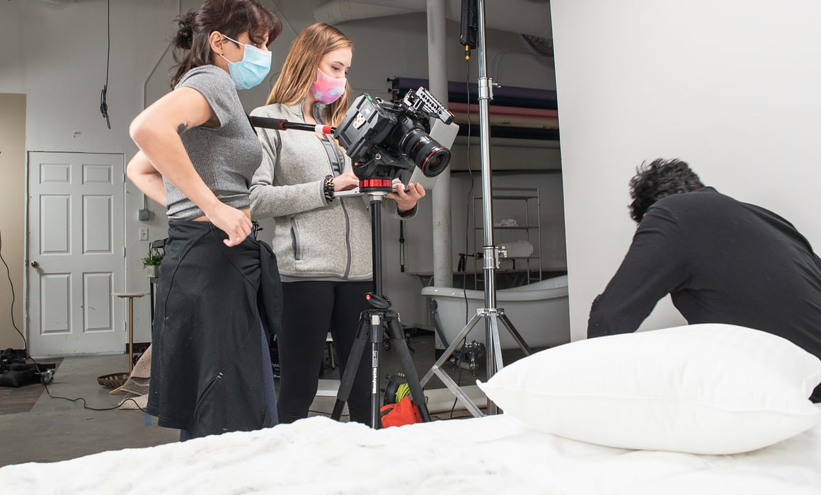 Two women looking through a camera at a man sitting on a bed holding a pillow.