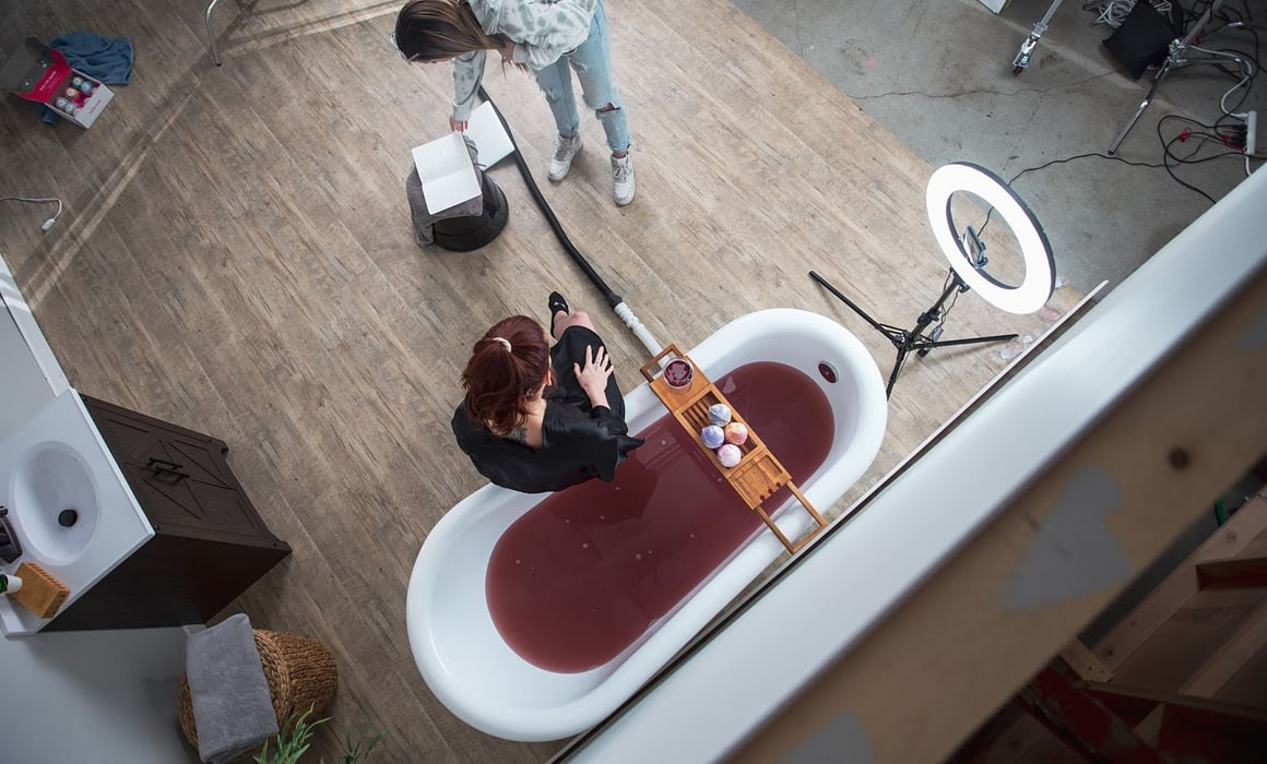 camera crew setting up around a bath filled with red fluid