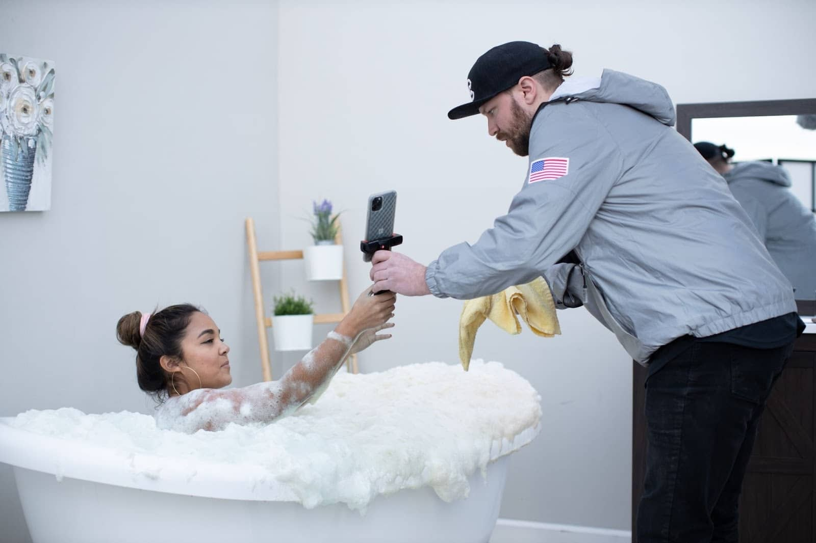 Man wearing a gray hoodie handing a camera to a woman sitting in a white bathtub